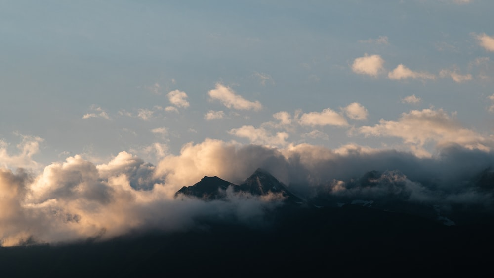 white clouds over mountain ranges