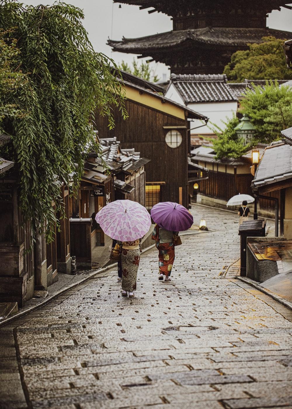 woman in pink umbrella walking on sidewalk during daytime