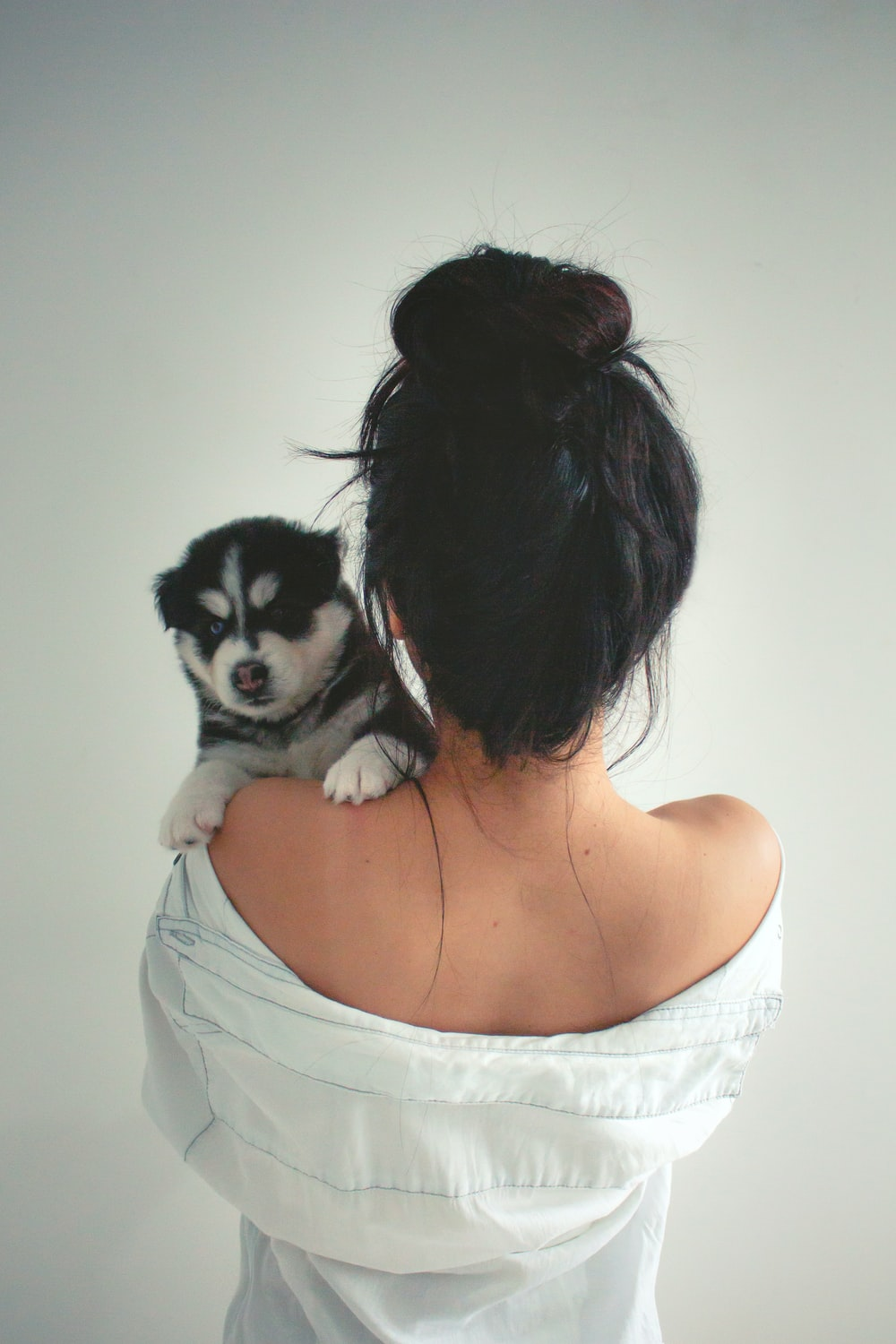 woman in white tank top carrying black and white puppy