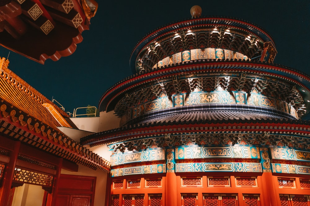 gold and red temple during night time