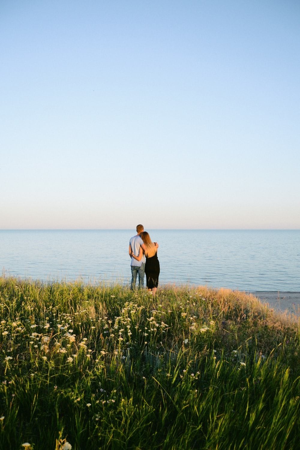 woman in black tank top and black pants standing on green grass field near body of near on near on