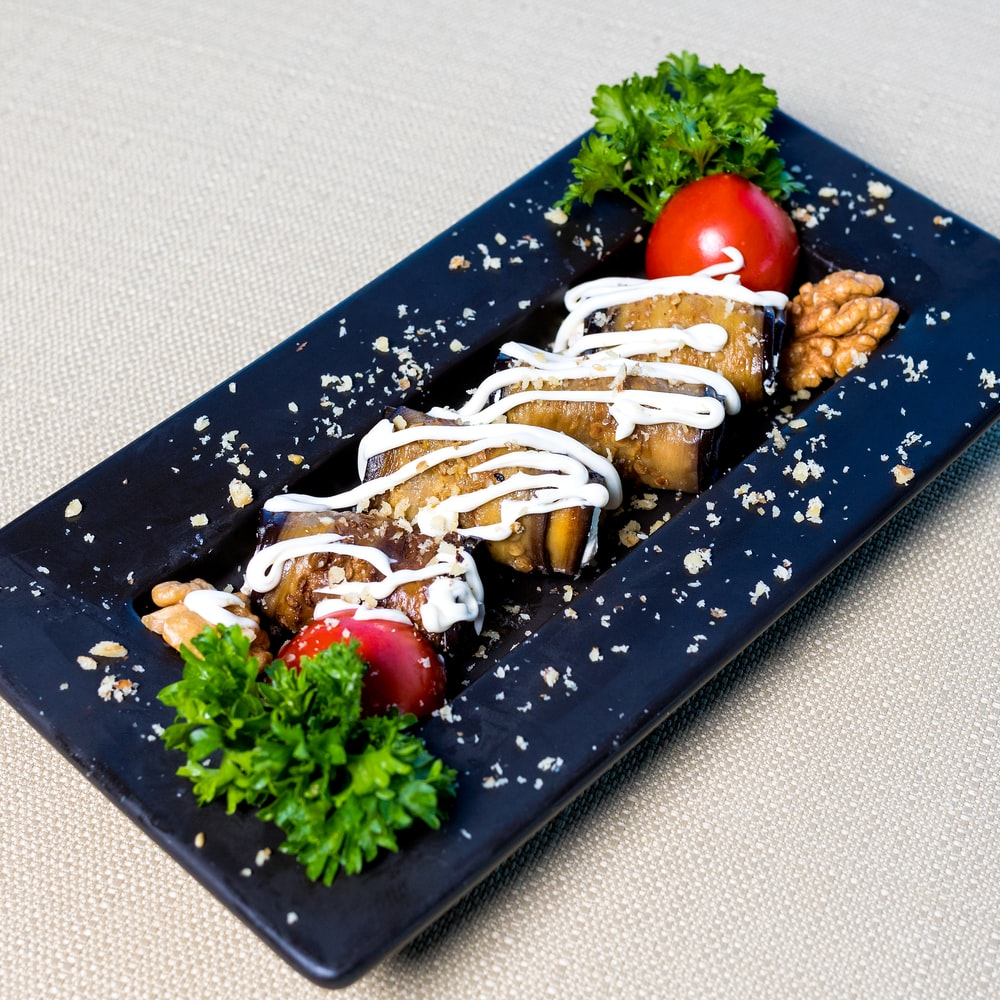 brown bread with white cream and green vegetable on black rectangular tray