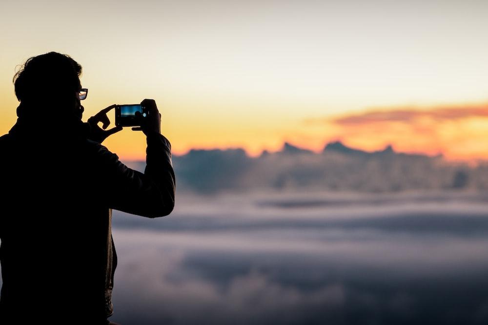 person holding black dslr camera during sunset