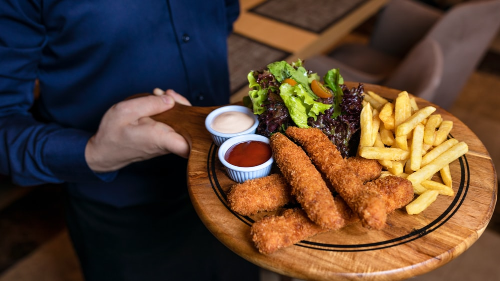fried food with green vegetable on brown wooden round plate