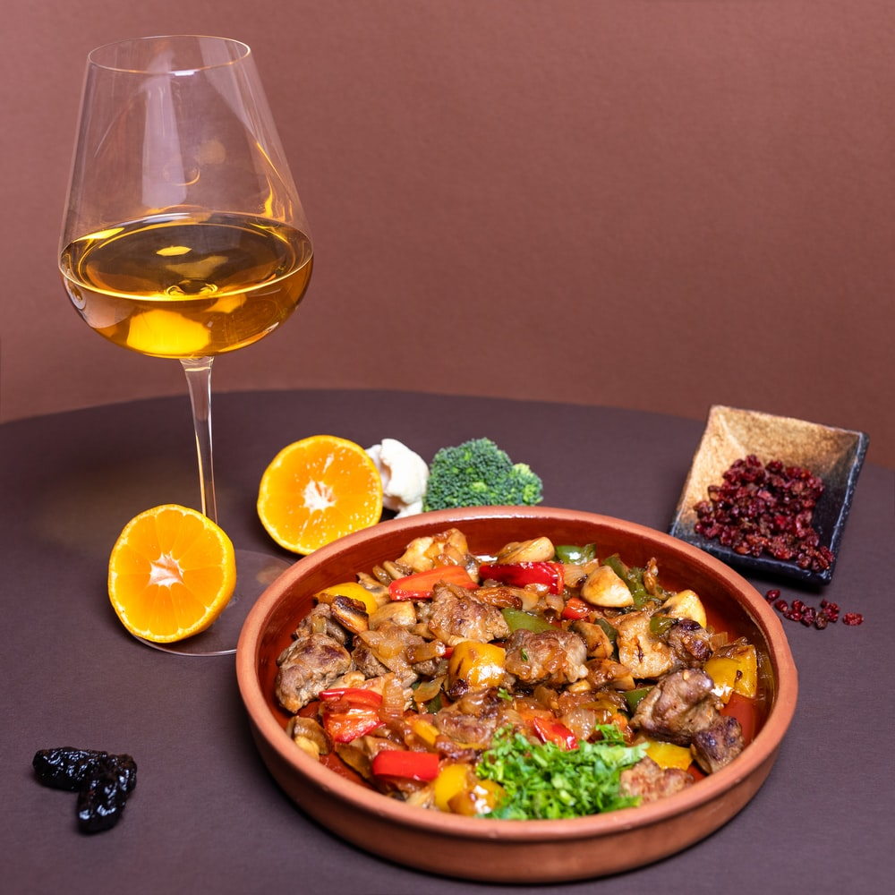 vegetable salad on brown ceramic bowl beside clear wine glass