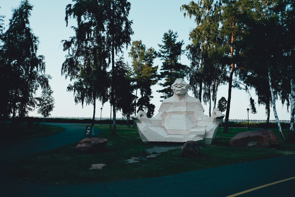 white statue on green grass field near green trees during daytime