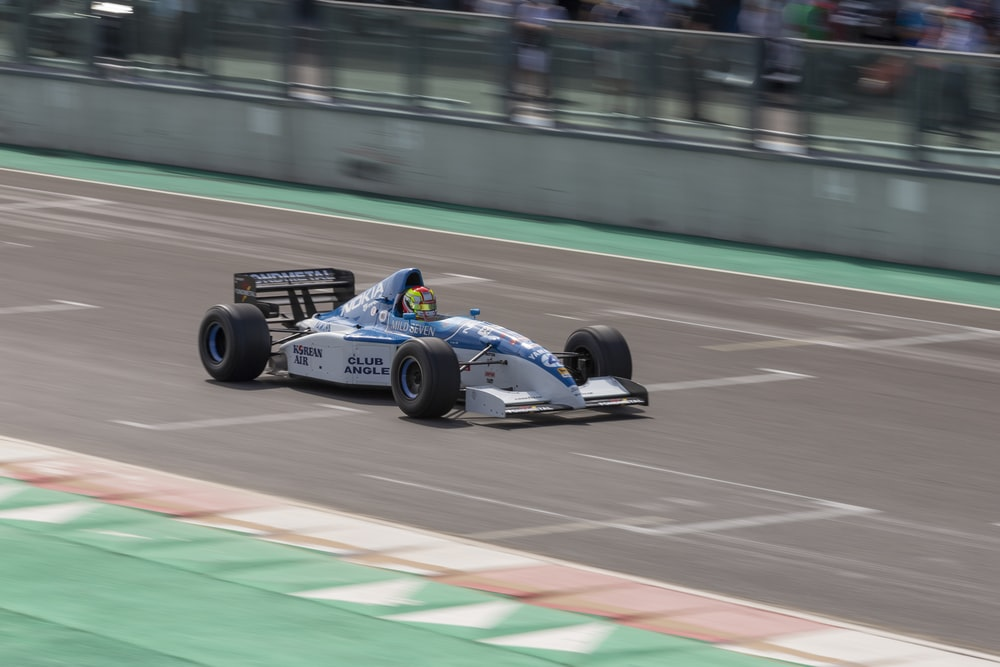 blue and white f 1 car on track
