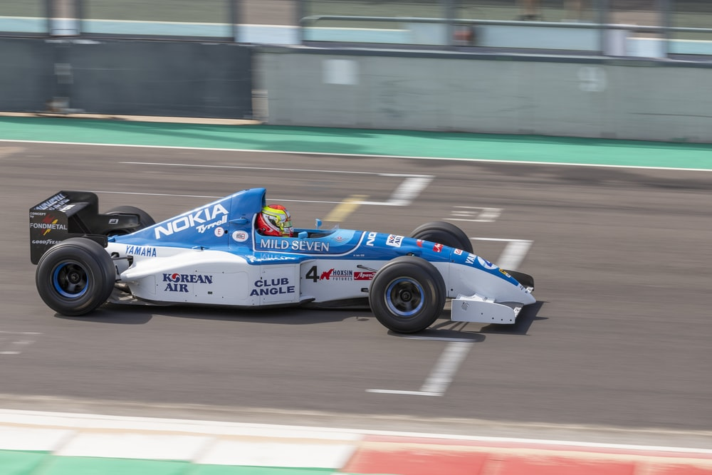 blue and white f 1 car on road