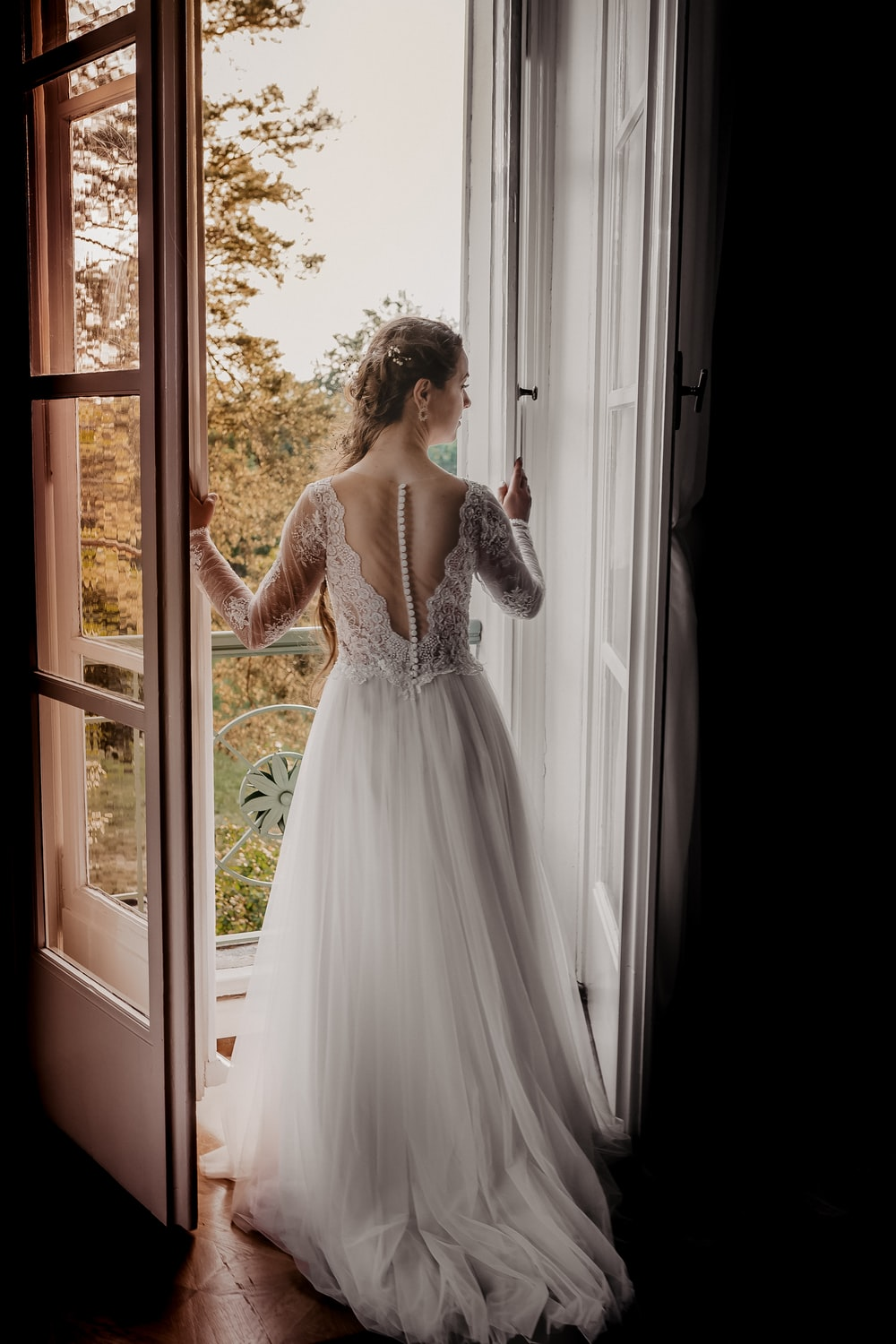 woman in white floral dress standing beside window during daytime