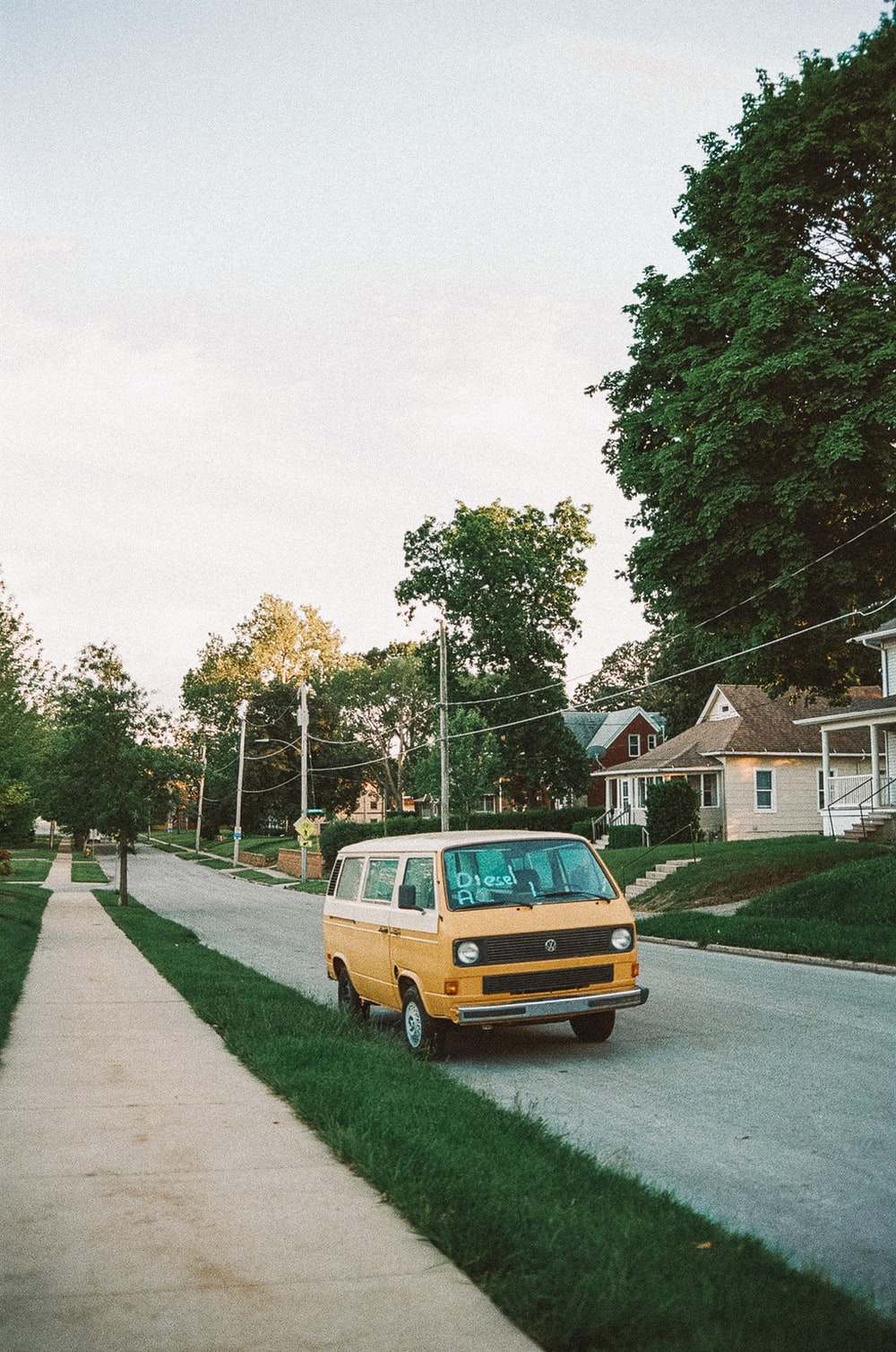 yellow van parked on green grass field near houses and trees during daytime