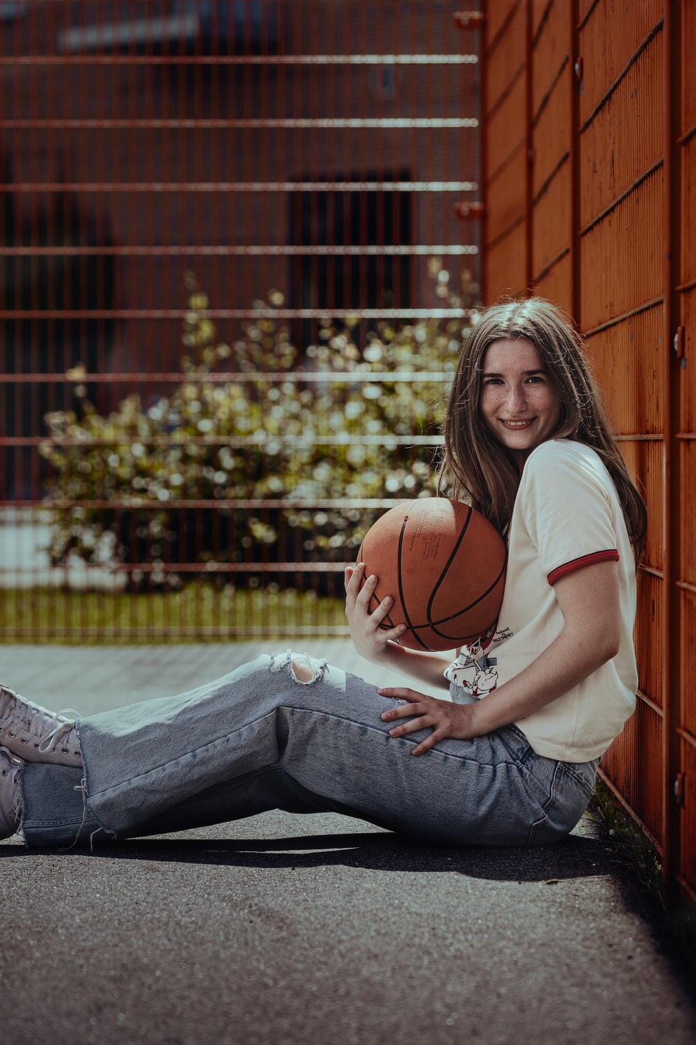 woman in white t-shirt and blue denim jeans sitting on basketball court