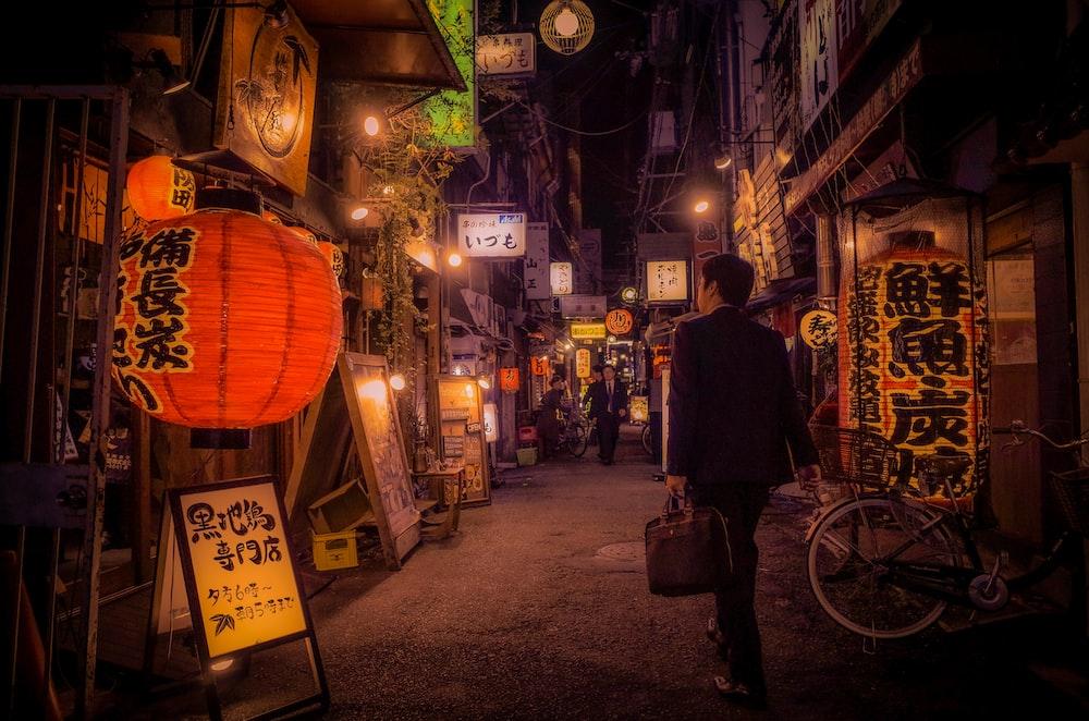 man in black jacket standing beside brown lantern during nighttime