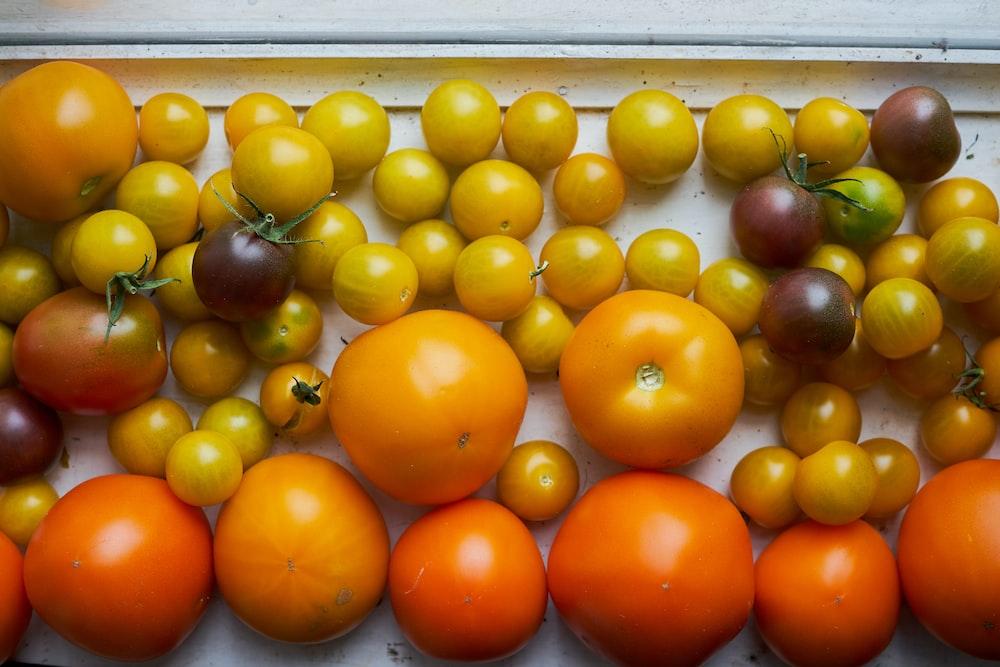 orange fruits on white plastic container