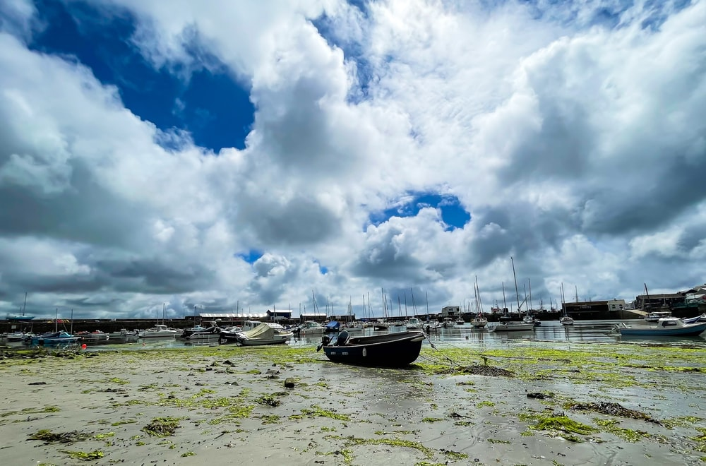 white and black boat on sea under white clouds and blue sky during daytime