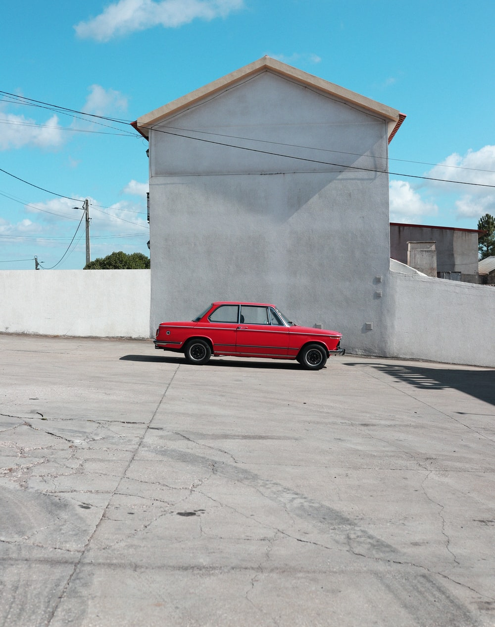 red coupe parked beside white wall