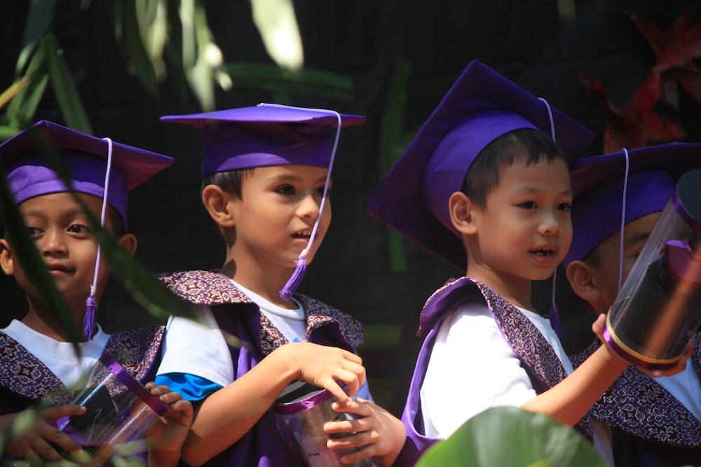 boy in academic gown standing beside girl in academic dress