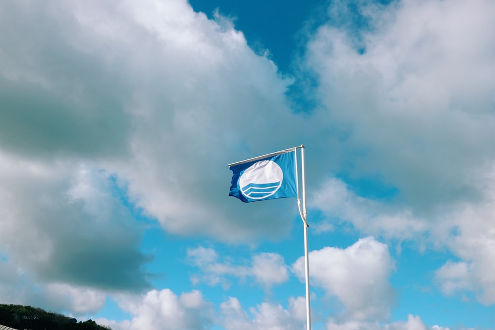blue and white flag under white clouds