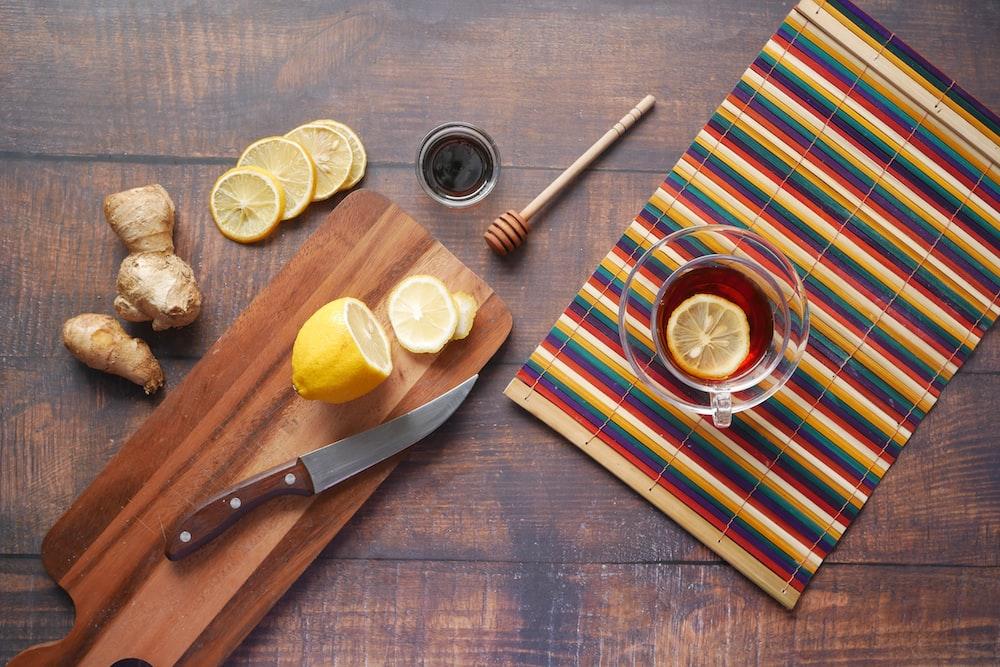 sliced lemon on chopping board beside knife and fork