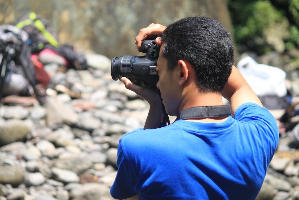 man in blue shirt holding black dslr camera