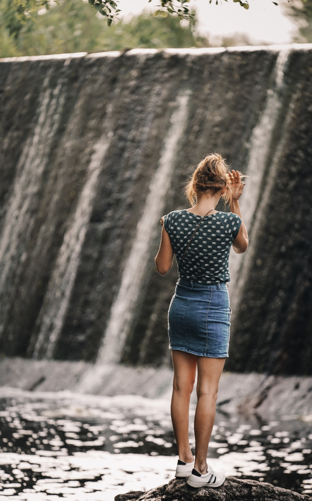 woman in blue and white polka dot dress standing in front of waterfalls during daytime