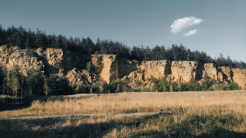 brown grass field near brown rock formation under blue sky during daytime
