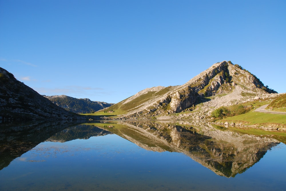 green and brown mountain beside lake under blue sky during daytime