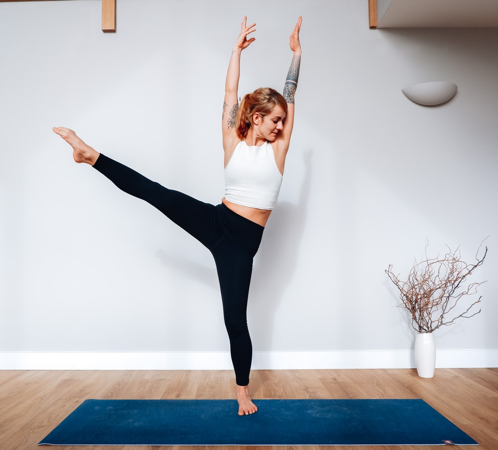 woman in white tank top and black leggings standing on blue yoga mat