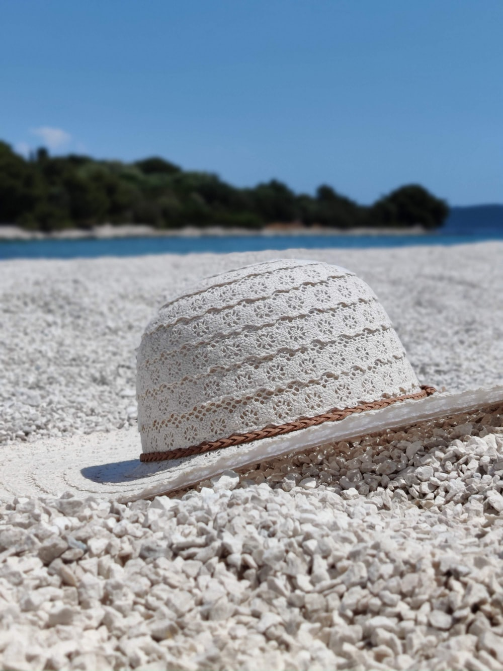 white and blue sun hat on white sand beach during daytime