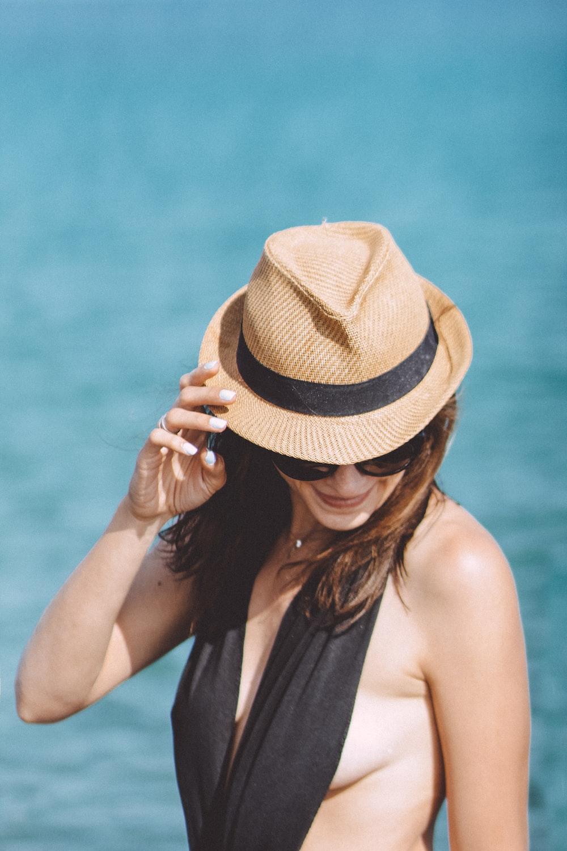woman in black tank top wearing brown fedora hat