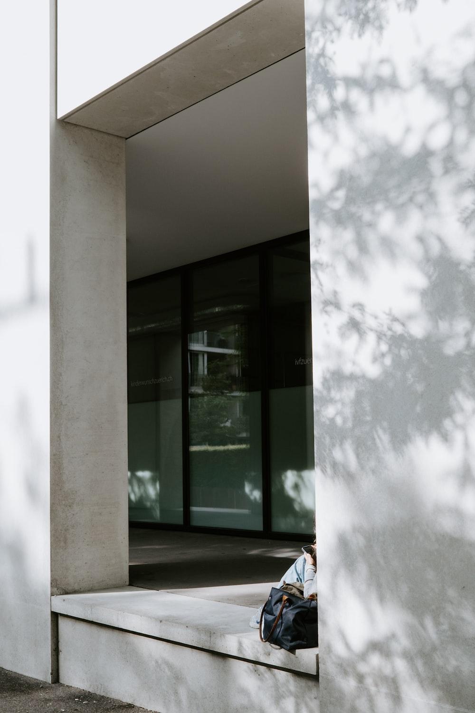 white concrete wall near glass window