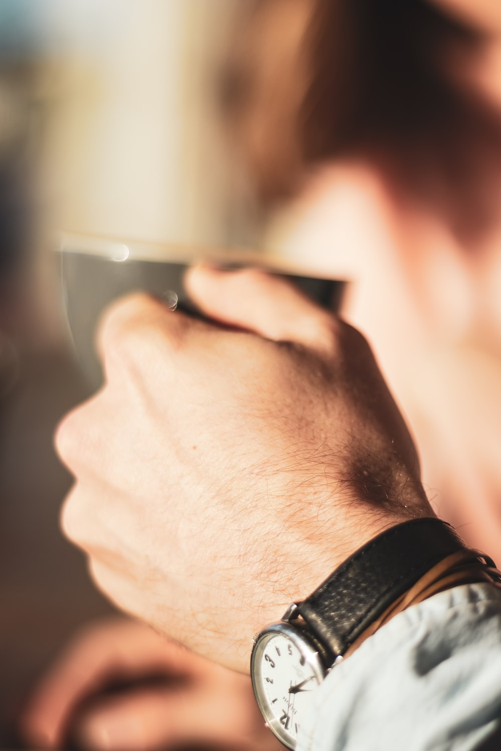 person wearing black watch holding clear drinking glass