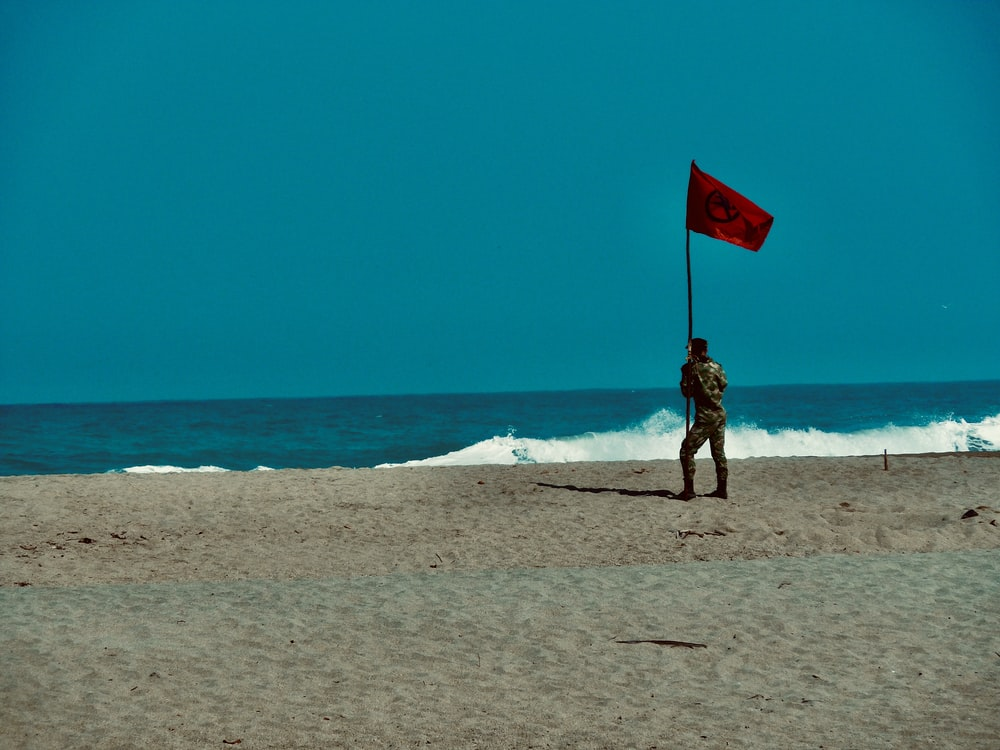 woman in black and white dress holding red flag standing on beach during daytime