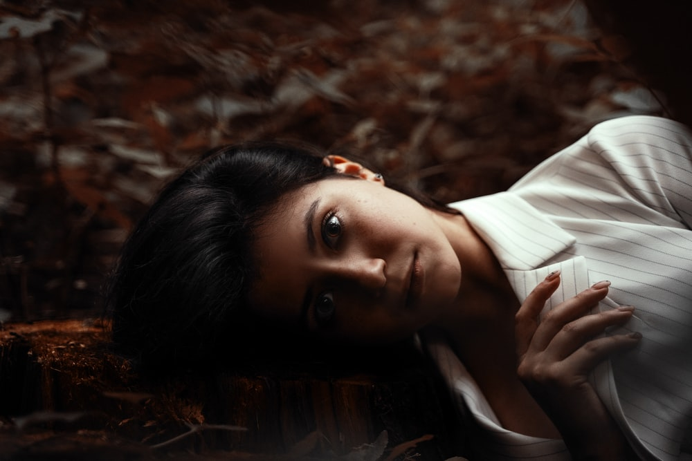 woman in white button up shirt lying on dried leaves