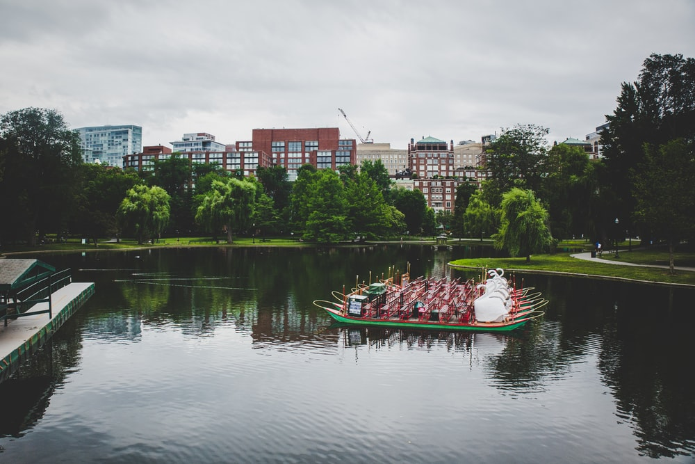 red and white boat on water near city buildings during daytime
