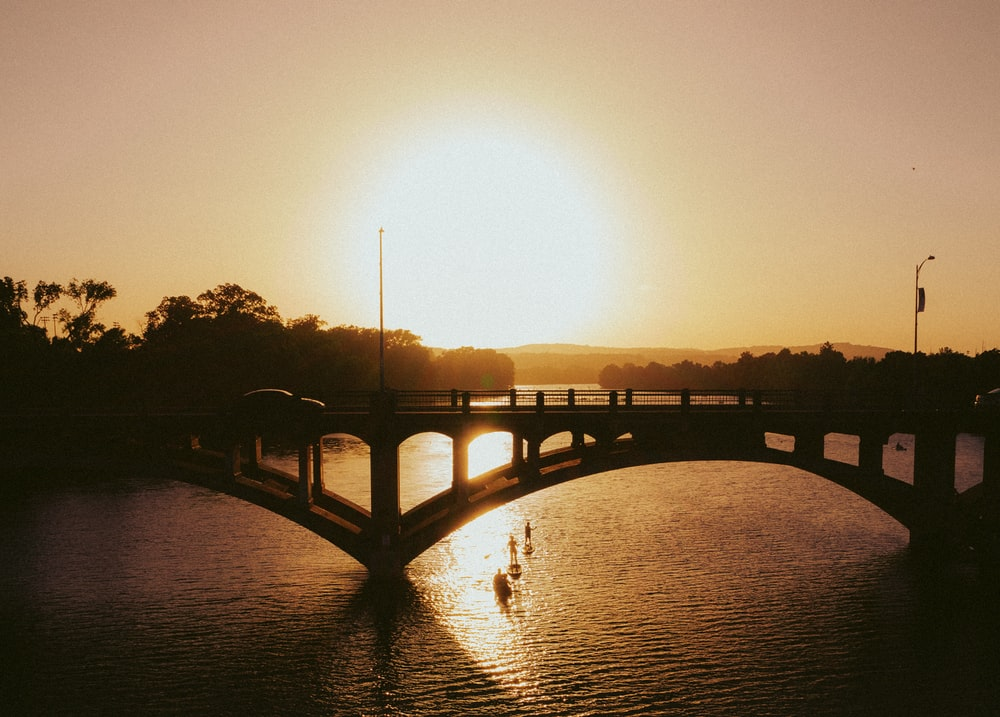 silhouette of bridge over water during sunset