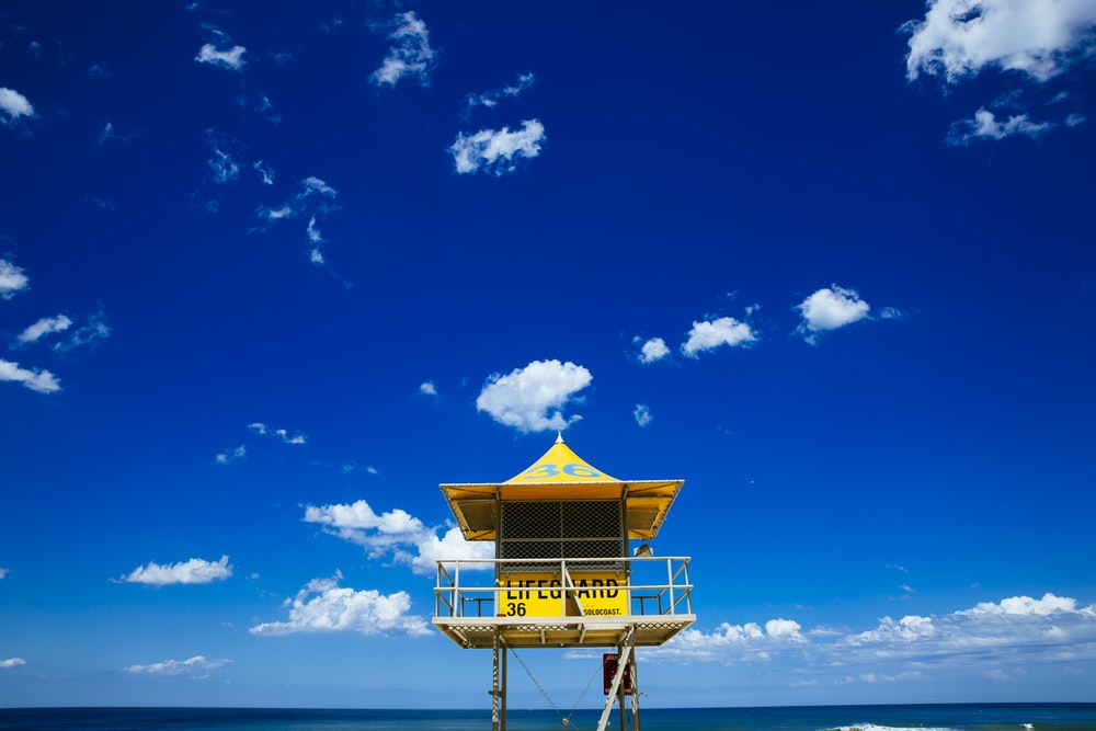 brown wooden lifeguard house on beach under blue sky during daytime