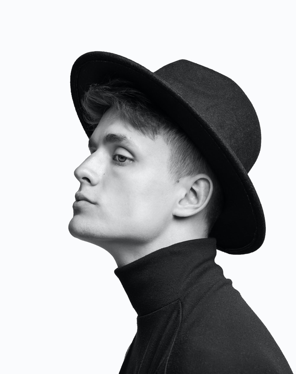 grayscale photo of man wearing black hat