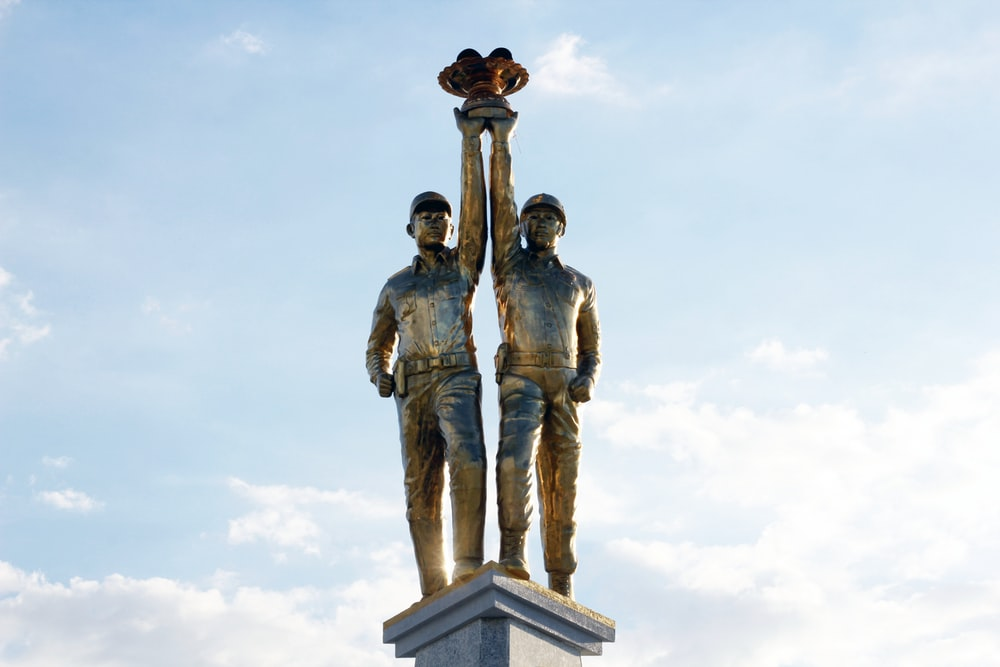 man and woman statue under white clouds during daytime