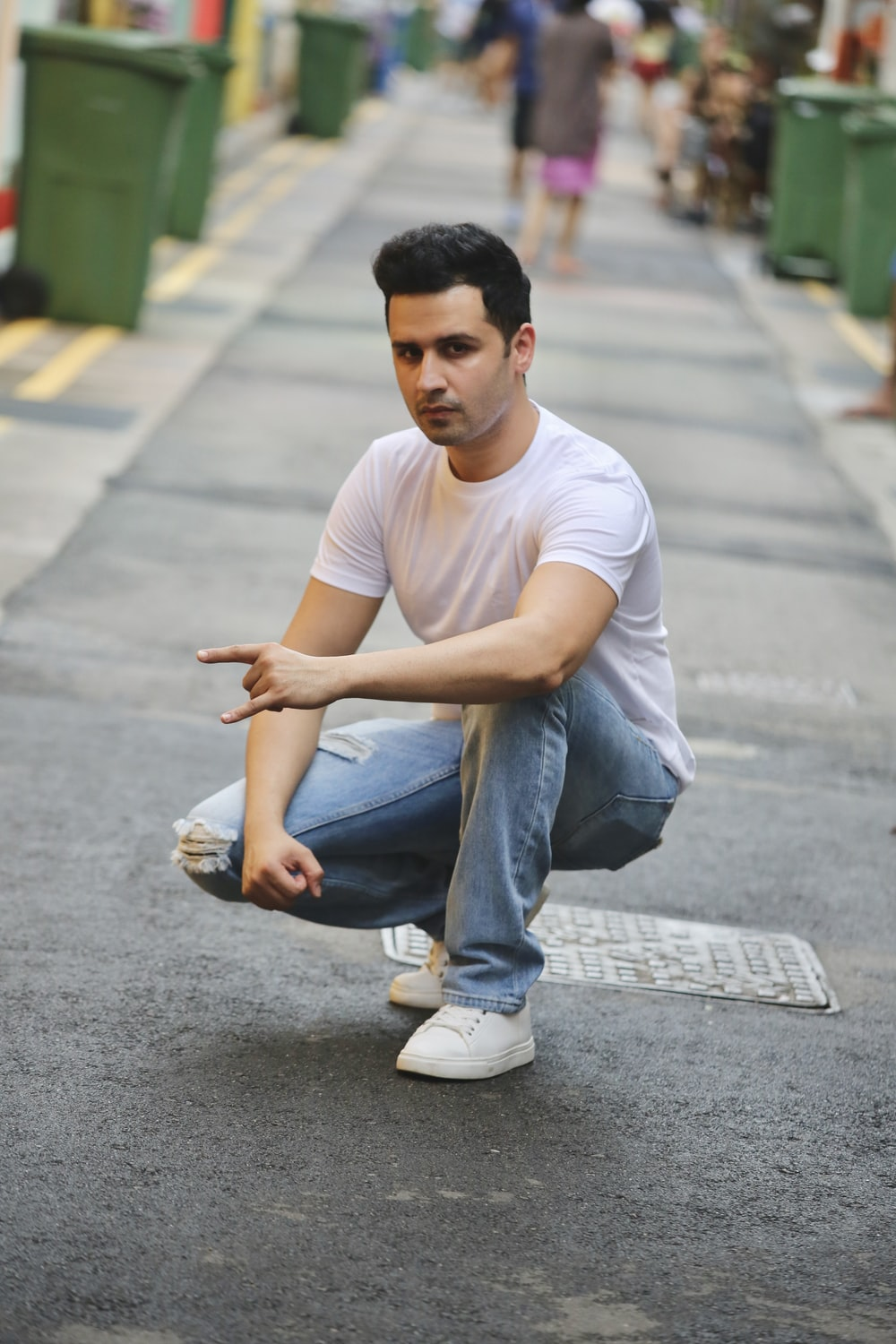 man in white crew neck t-shirt and blue denim jeans sitting on gray concrete road
