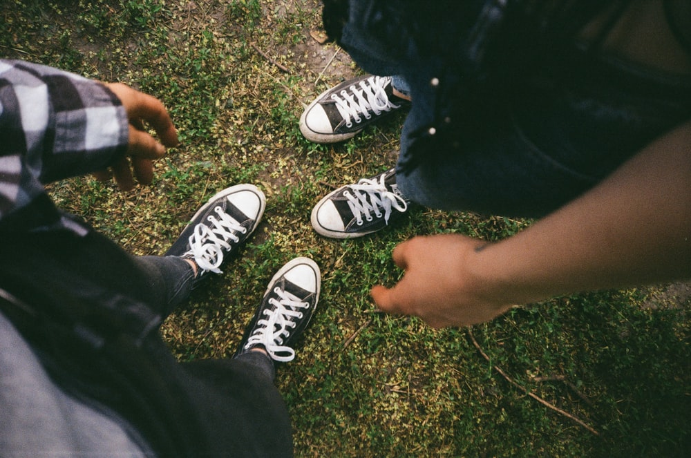 person wearing black and white converse all star low top sneakers