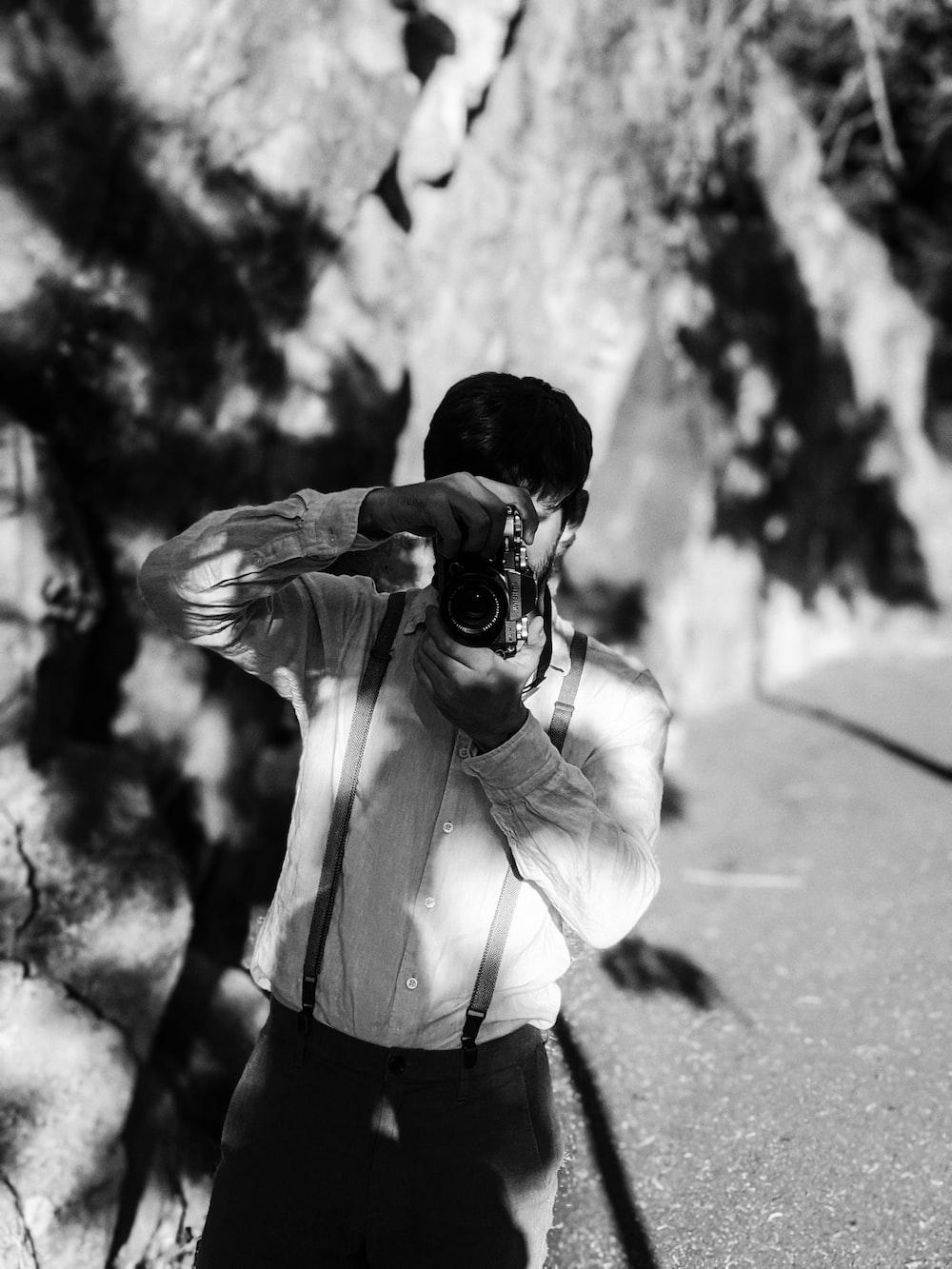 man in white dress shirt holding camera