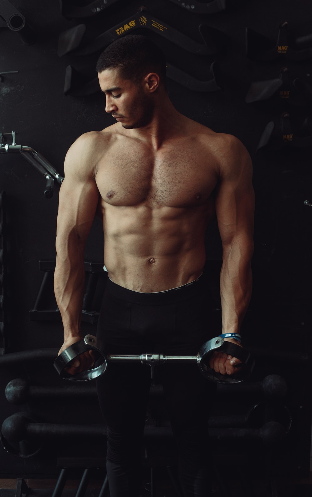 topless man in black shorts holding black and silver dumbbell