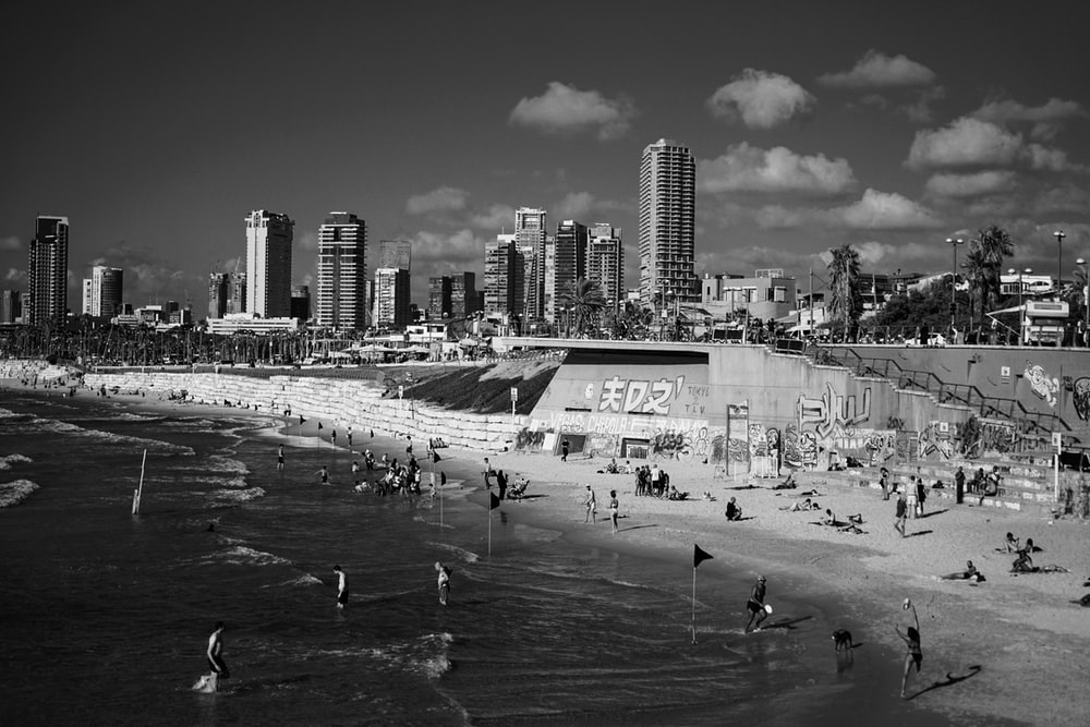 grayscale photo of people on beach near city buildings