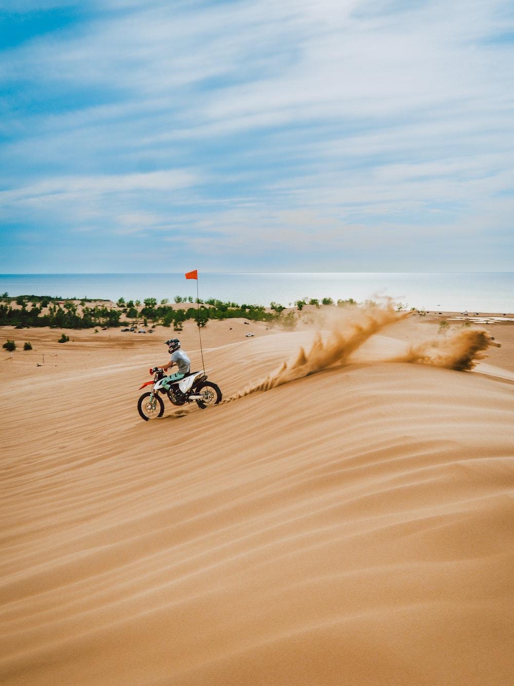 man riding motorcycle on brown sand during daytime