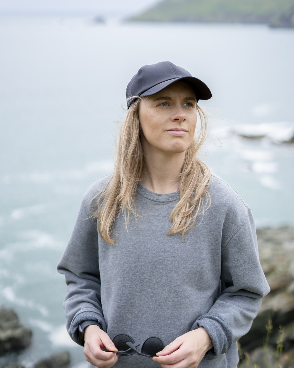 woman in gray long sleeve shirt and black cap