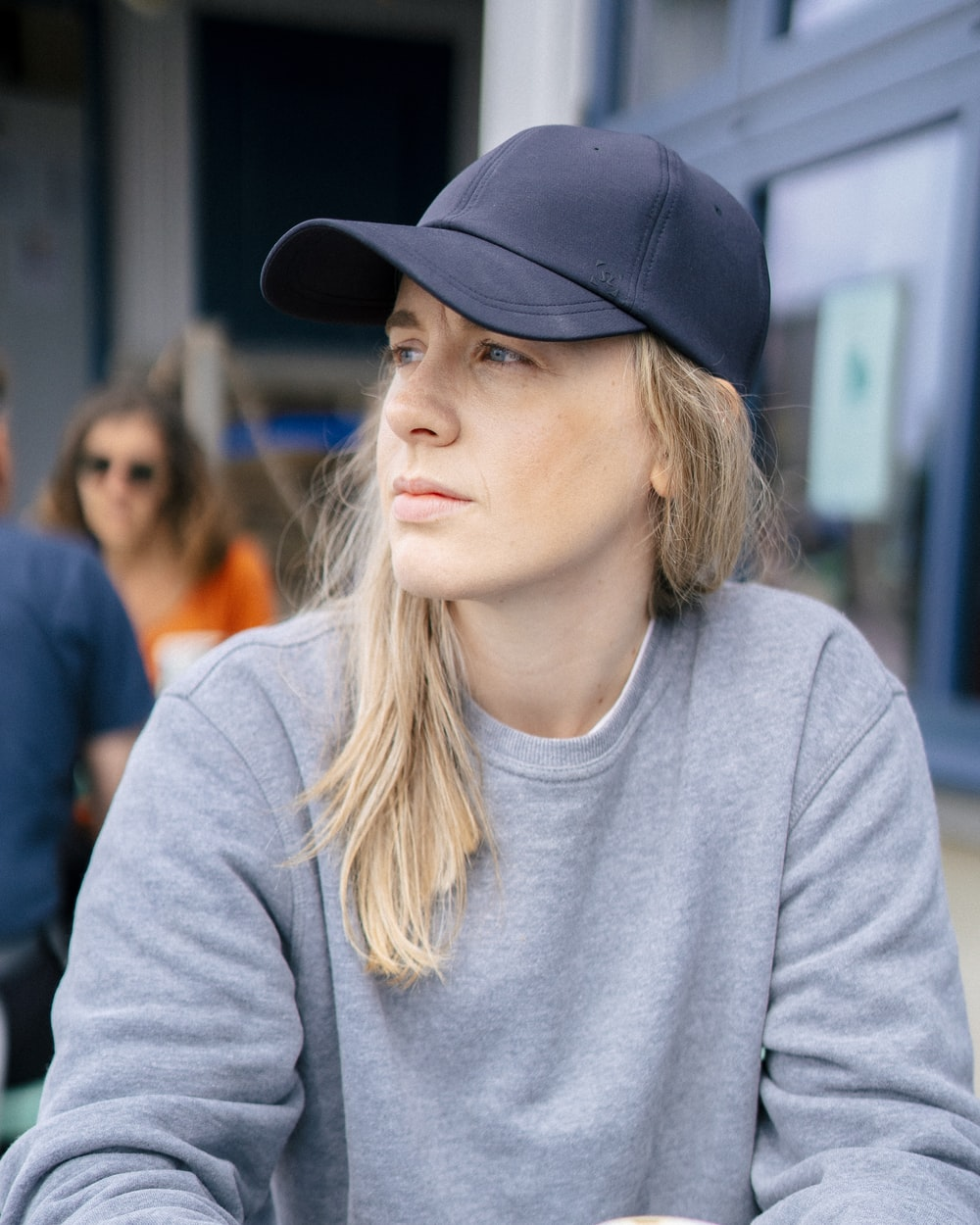 woman in gray sweater wearing black cap
