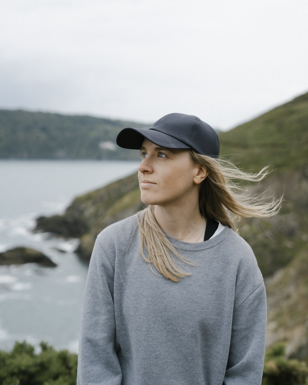 woman in gray sweater and black fedora hat standing near body of water during daytime