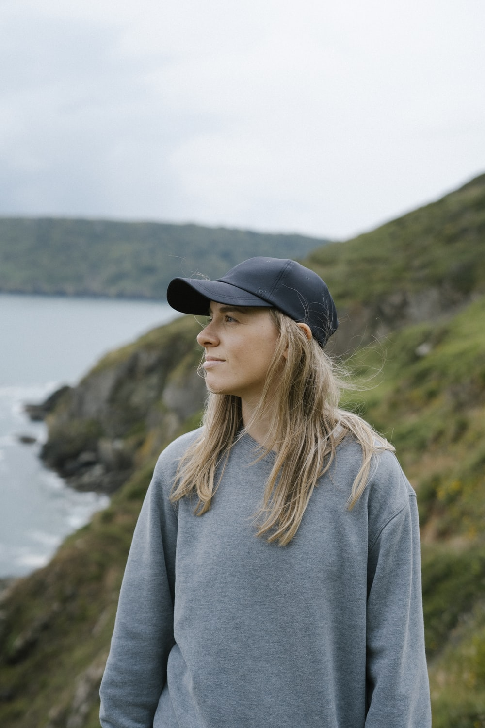 woman in gray long sleeve shirt and black hat standing near body of water during daytime