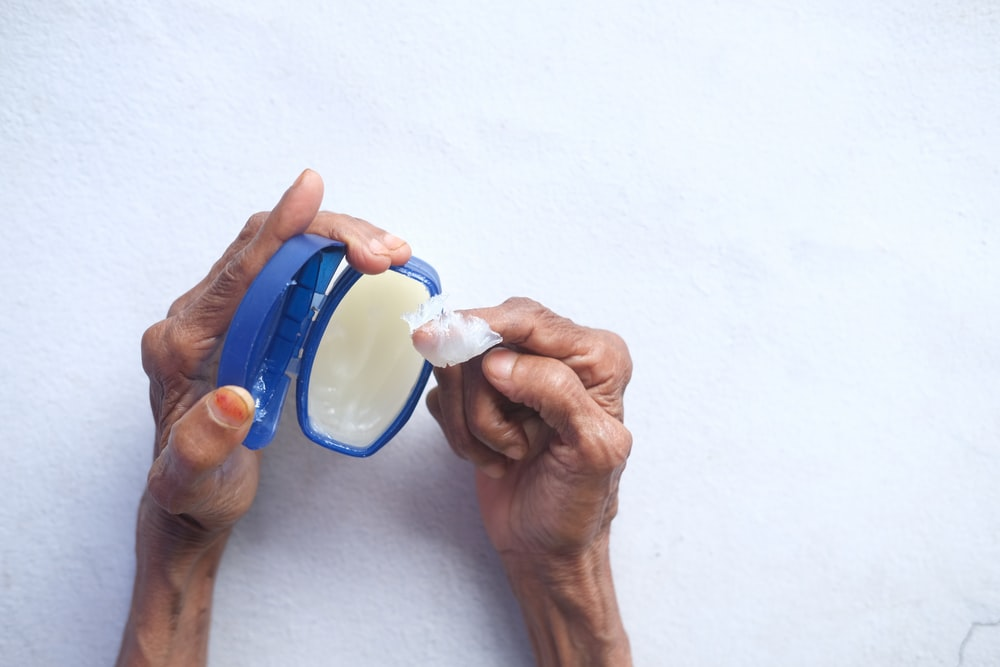 person holding blue and white plastic container