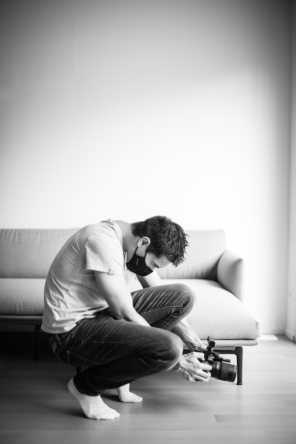 man in white t-shirt and black denim jeans sitting on couch
